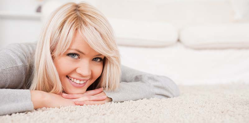 Charming Blond Woman Lying Down On a Carpet in the Living Room