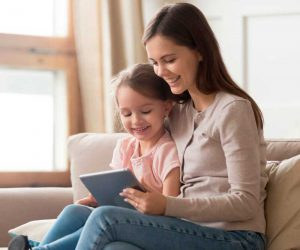 Happy Mom and Kid Daughter Using Digital Tablet Sitting on Sofa