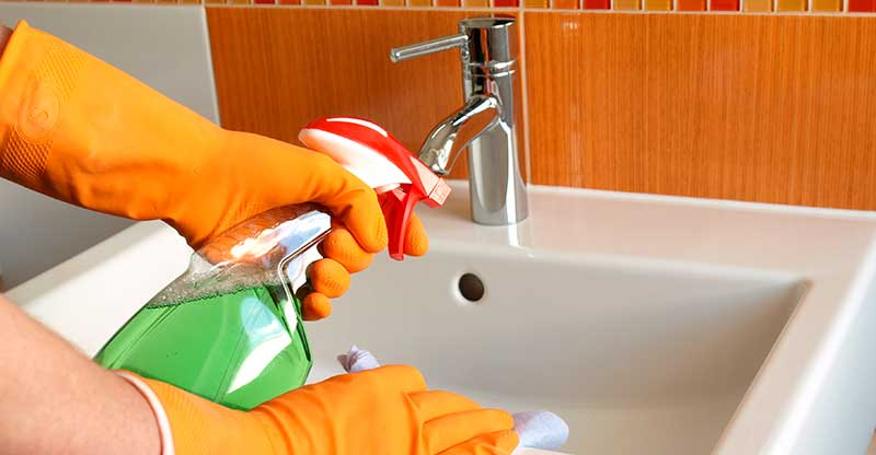 Woman Cleaning the Bathroom Sink with a Damp Cloth